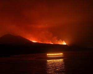 Coastguards pass as lava is seen arriving at the sea following the eruption of a volcano, seen...