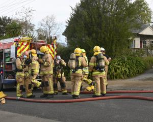 Fire and Emergency New Zealand firefighters mop up after a house fire in Warrington on Saturday...