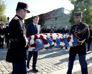French President Emmanuel Macron (c) lays a wreath near the Pont de de Bezons, Bezons bridge,...