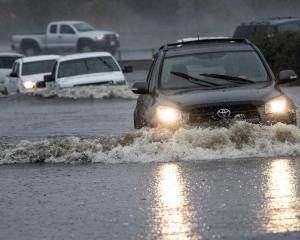 Vehicles drive through a flooded area in Fairfield, California. Photo: Reuters