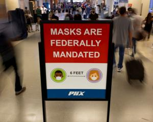 Travellers make their way past a sign mandating face masks at Phoenix International Airport in...