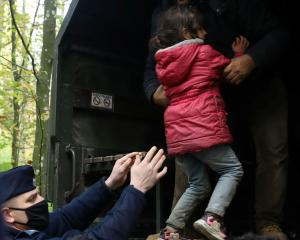 Iraqi migrants are put on a military truck after being caught by border guards and police...
