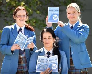 Holding up copies of their recently published mental health guidebook are Queen's High School...
