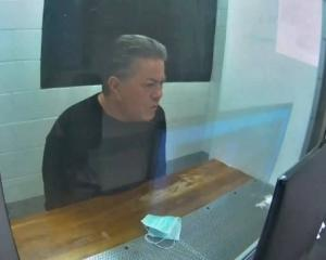 Destiny Church leader Brian Tamaki sits in a holding cell while attending his latest hearing via...