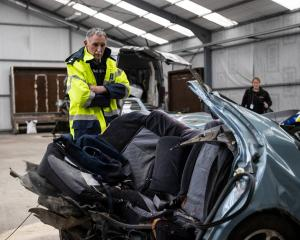 Inspector Dave Gaskin looks over the car, which was ripped in half by the impact of a crash in...