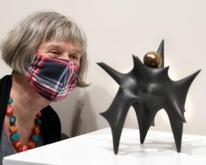 Otago Art Society volunteer Moira Styles admires a Rick Rudd teapot from the Ceramic Association...