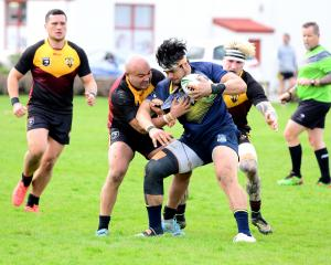 Otago Whalers player Tofatu Solia is on the receiving end of a tackle by Southland Rams defenders...
