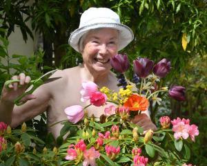 Gillian Vine in her flower garden on National Nude Gardening Day. PHOTO: STEPHEN JAQUIERY