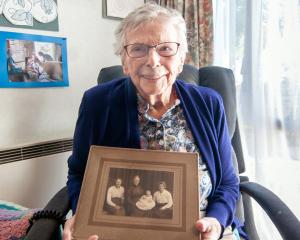 Dulcie Armitage, of Alexandra, holds a photo of herself as a baby with her mother, grandmother...