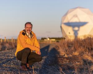 Robin McNeill stands in front of one the 35 antennas at Space Operations New Zealand's Awarua...