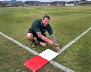 Volunteer Matt Thomson puts down a base at Hancock Park yesterday in the last of the preparations...