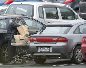 A supermarket shopper loads groceries into her car at Countdown Dunedin Central yesterday...