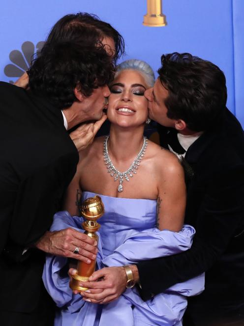 Lady Gaga is congratulated by Anthony Rossomando (left) and Mark Ronson for winning best song....