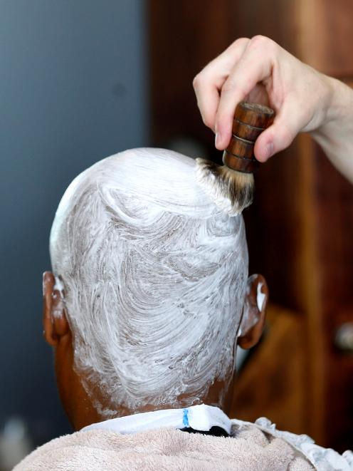 A client is prepared for shaving. Photo: Reuters