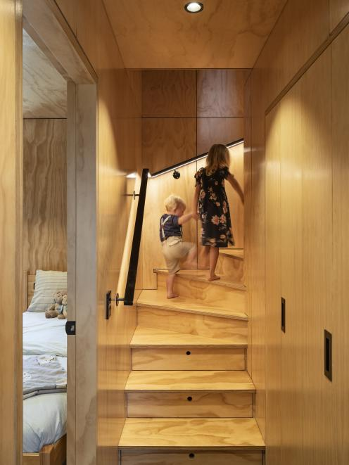 The built-in storage includes hidden cupboards and drawers within the steps of the stairs.