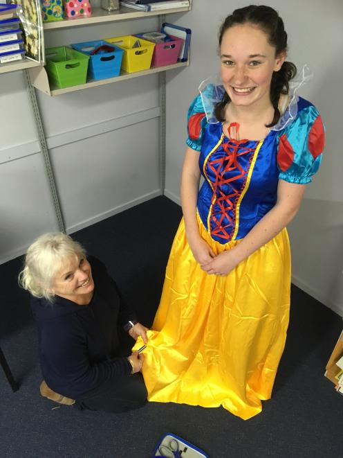 Backstage crew member Sue Scott (left) adjusts Lucy Neilson's hem in preparation for her role....