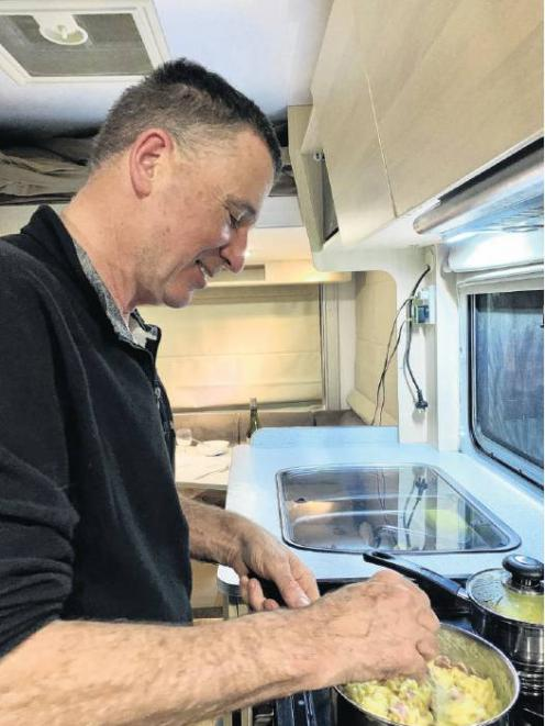 Chris cooks dinner in our warm and cosy Maui motorhome, a vast contrast to the conditions endured...