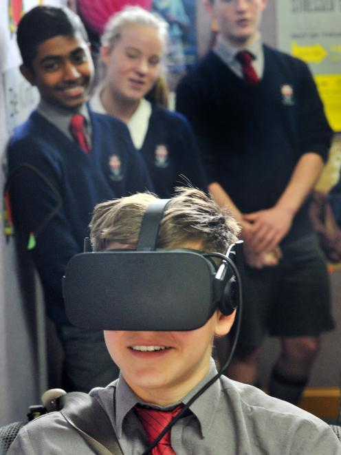 Kavanagh College pupil Alberto Adams (13) uses the CoDriVR driving simulator, while fellow pupils...