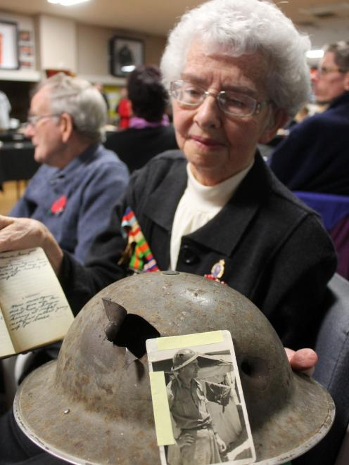 Carol Cosgrove, of Invercargill, holds the steel army helmet her father, George James Kennedy of...