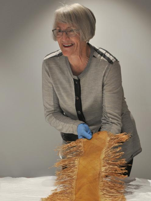 Mary Gray has her first view of Polynesian textile items found by her grandfather in a cave near...