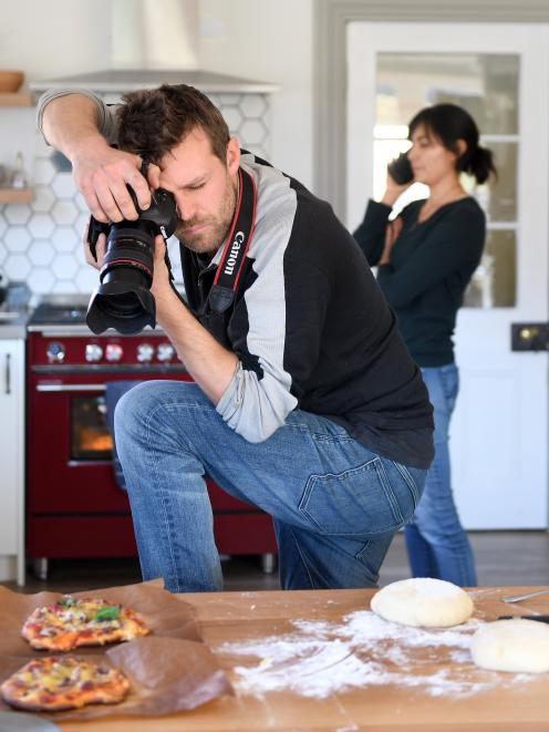 Carlos Bagrie photographs pizza for their lockdown book while Nadia Lim deals with a phone call...