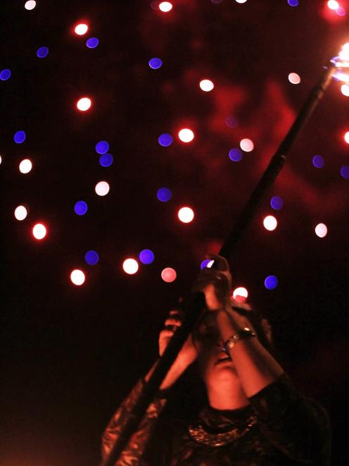 Shannon Wetdewich, of the Dunedin Fire and Circus Club, performs in Wansbeck St as fireworks...