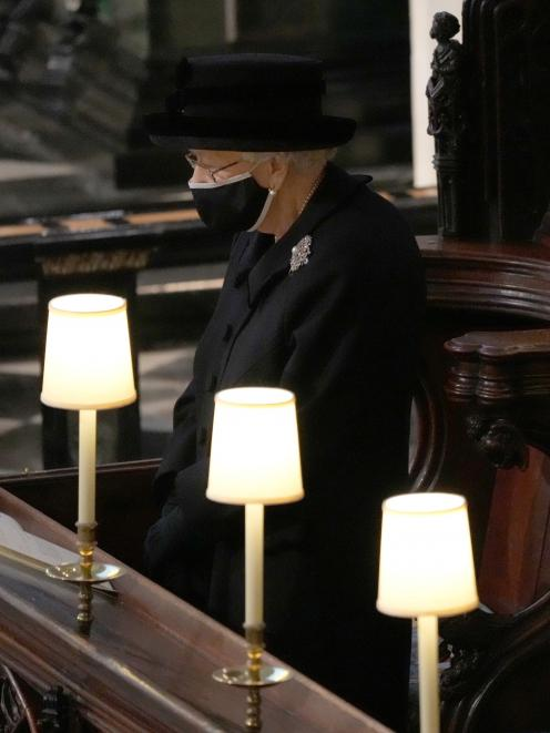 The Queen was forced to sit alone and wear a mask due to Covid-19 measures. Photo: Reuters