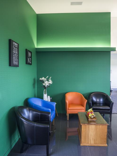 Resene Camarone feature wall with colour pops through accent cushions.  Project by Robert Caldana...