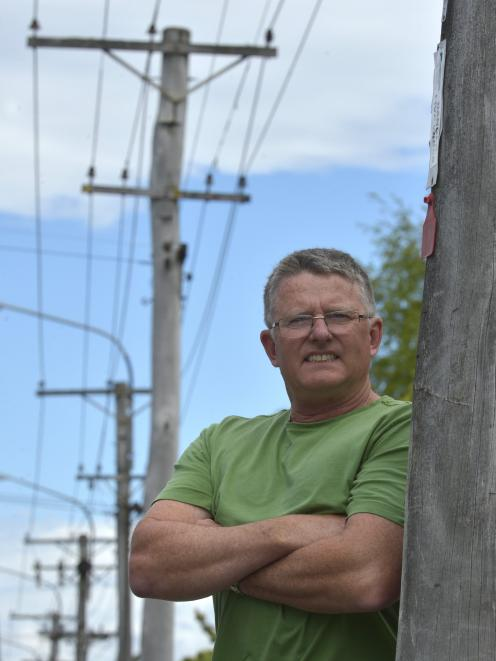 Geoff Lyell beside a  red-tagged power pole in North Rd, Northeast Valley. Photo: Gerard O'Brien.