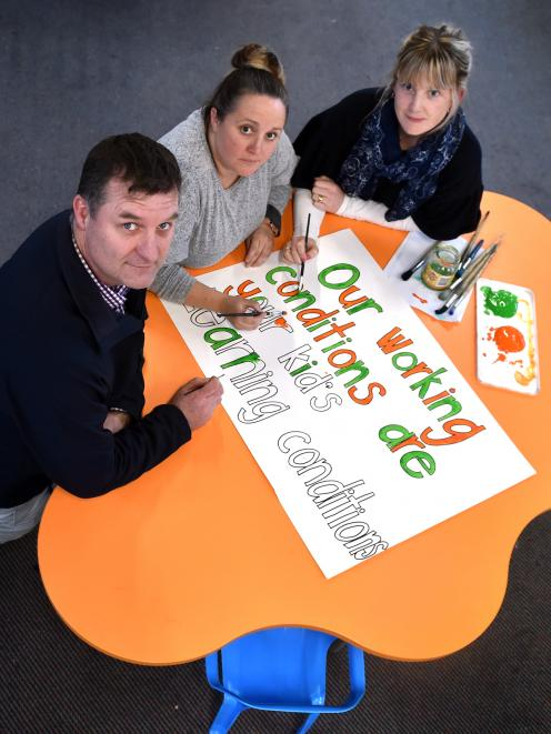 Elmgrove School principal Chris McKinlay and teachers (from left) Carlie Sinclair and Melissa Haggerty paint signs for today's NZEI union strike. Photo: Peter McIntosh