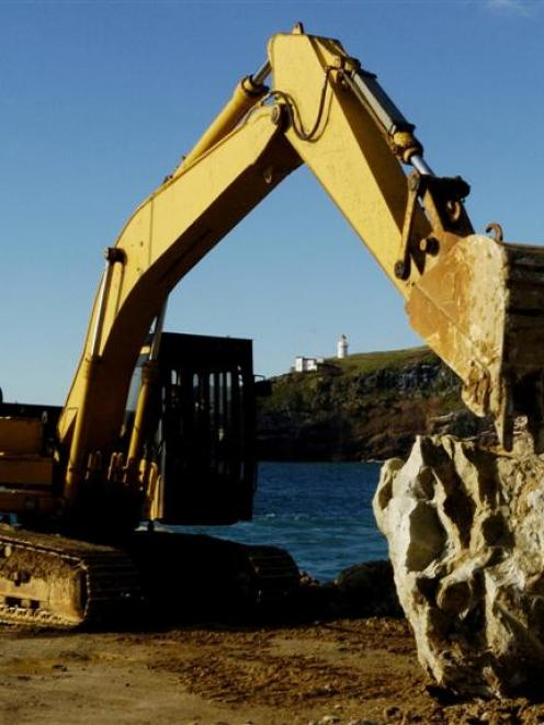A digger moves a large boulder into place during repair work to the Aramoana mole. Photo by...