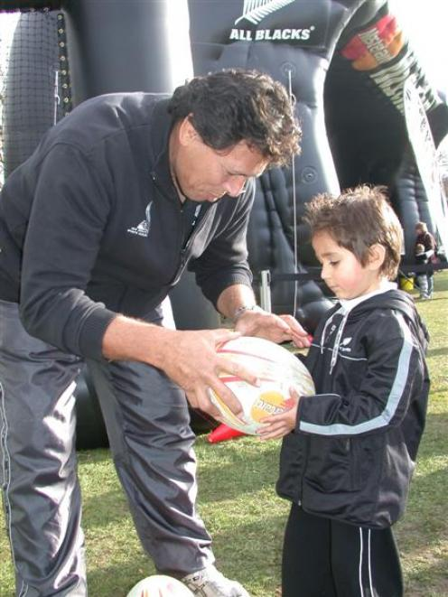 Leon Searle (4) of Oamaru, gets advice on passing from All Blacks great Buck Shelford at the All...