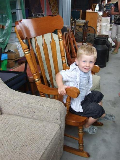 James Gare  (2), of Alexandra, tries out a rocking chair during one of three auctions and garage...