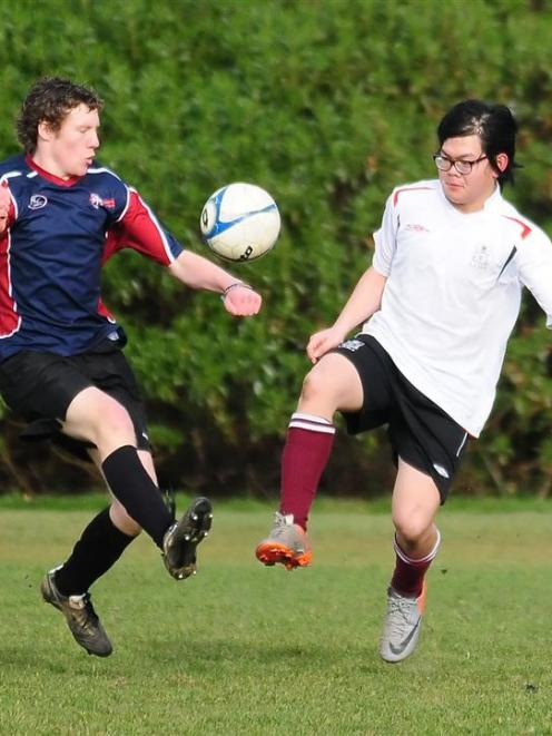 Matt Kelly (Kavanagh, left) and Tam Tangdham (Logan Park High) try to control the ball.