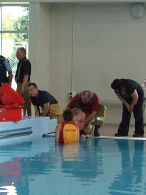 A 10-year-old boy trapped by his knee at the Balclutha Centennial Pool yesterday  is helped by a...