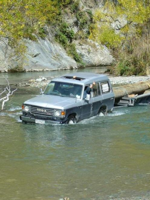 A 4WD completes one of 10 river crossings with two of the logs used to construct a bridge over...