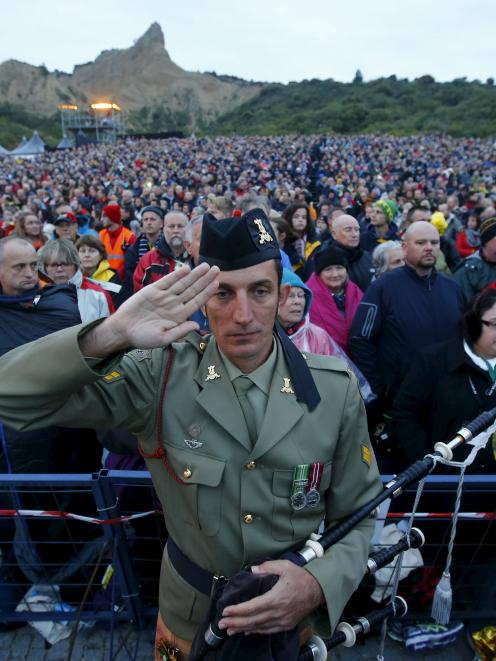 A bagpiper from the Australian army salutes during a dawn ceremony marking the 100th anniversary...