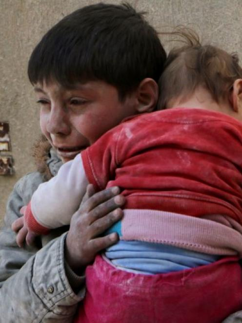 A boy holds his baby sister saved from under rubble, who survived what activists say was an...
