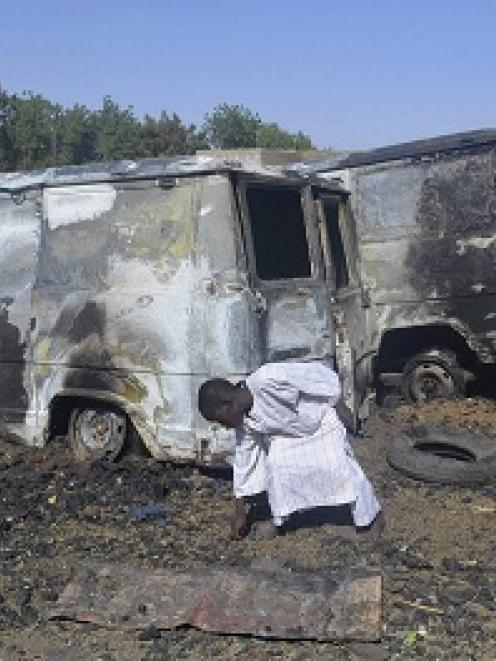 A boy searches the ground next to a burnt-out vehicle, caused by an attack from Boko Haram...