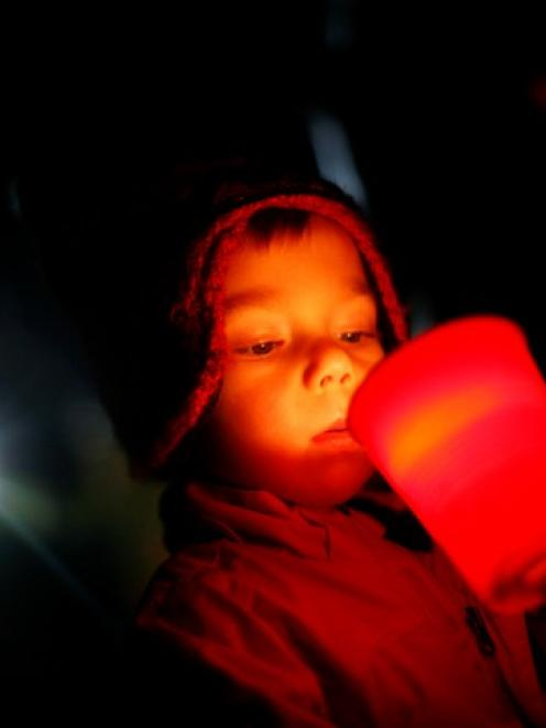 A boy takes part in a candlelight vigil in Newtown, Connecticut, on Friday, a week after a...