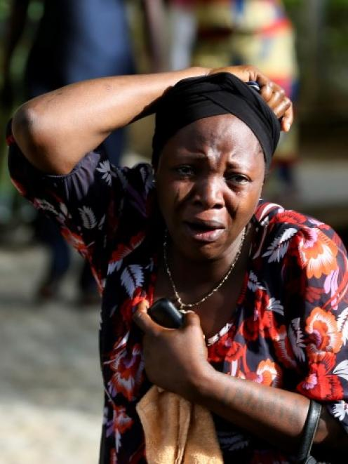 A bystander reacts as victims of the bomb blast arrive at the Asokoro General Hospital in Abuja....