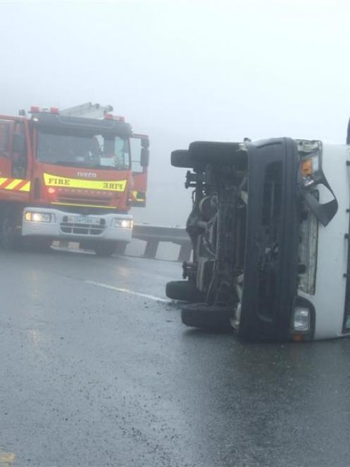 A  campervan  on its side blocks  a lane on the Crown Range Rd on Saturday. Photo by Christina...