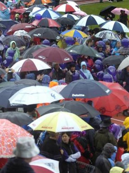 A carpet of umbrellas covers the athletics track at the Caledonian Ground, Dunedin, as cancer...