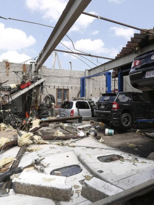 A collapsed roof is seen with damaged automobiles at a car workshop on Herman Street in Revere,...