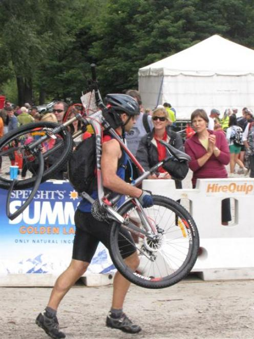 A competitor in the 2012 Motatapu mountain bike event is forced to carry his bike as he nears the...