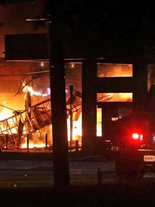 A convenience store burns during a night of rioting in Ferguson, Missouri after the death of...