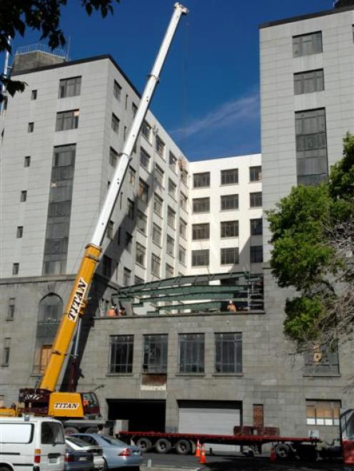 A crane lifts another steel beam into position at the rear of Dunedin's former chief post office...
