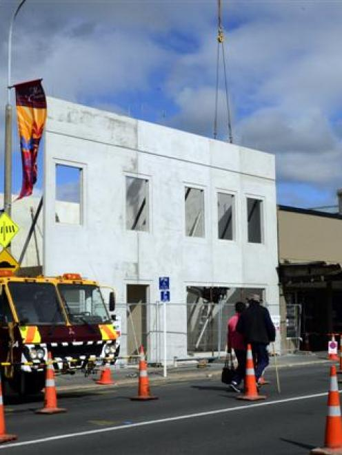 A crane lifts the new facade of the Brocklebank building in King Edward St, South Dunedin, into...