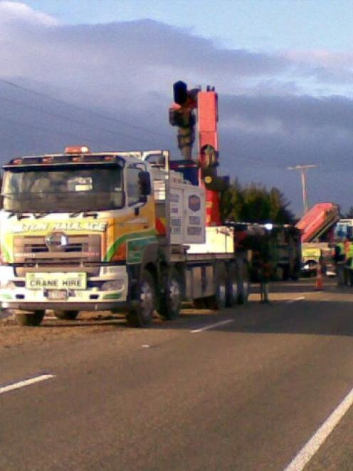 A crane truck is used to assist after a truck and trailer rolled off the road on SH1 near Hampden...