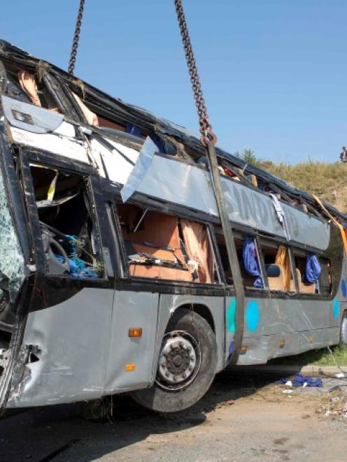 A crashed bus is loaded on a platform at the site of the accident on German A2 highway near the...